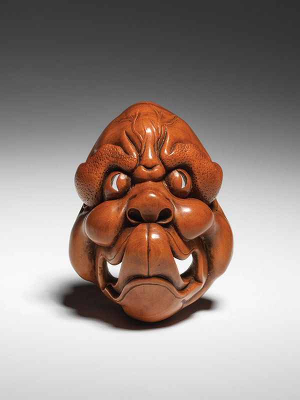 A small okinmono style carving of a mask