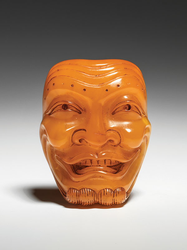 An amber Noh mask netsuke of Okina