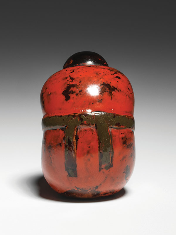 A lacquered netsuke of a sarubobo doll