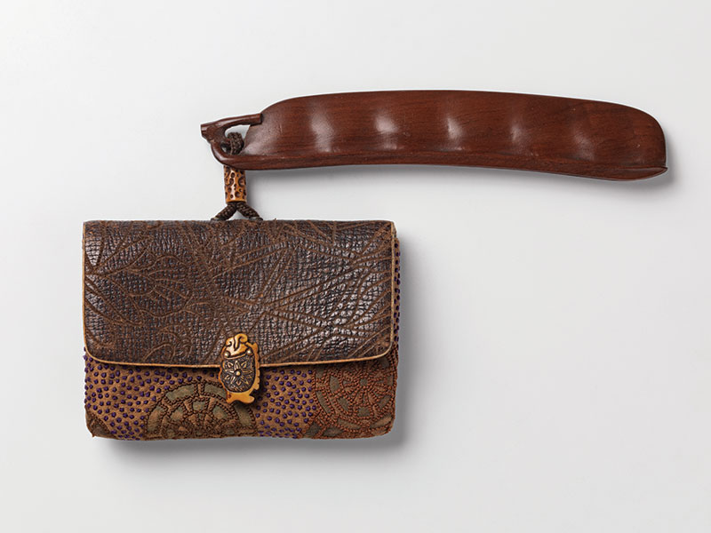 A tooled leather and fabric tobacco pouch