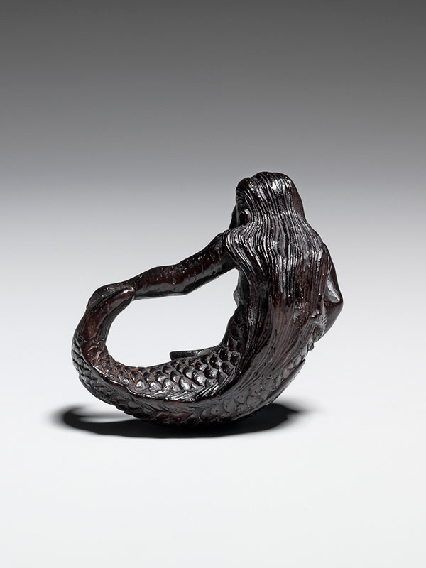 A ningyo mermaid grips her tail