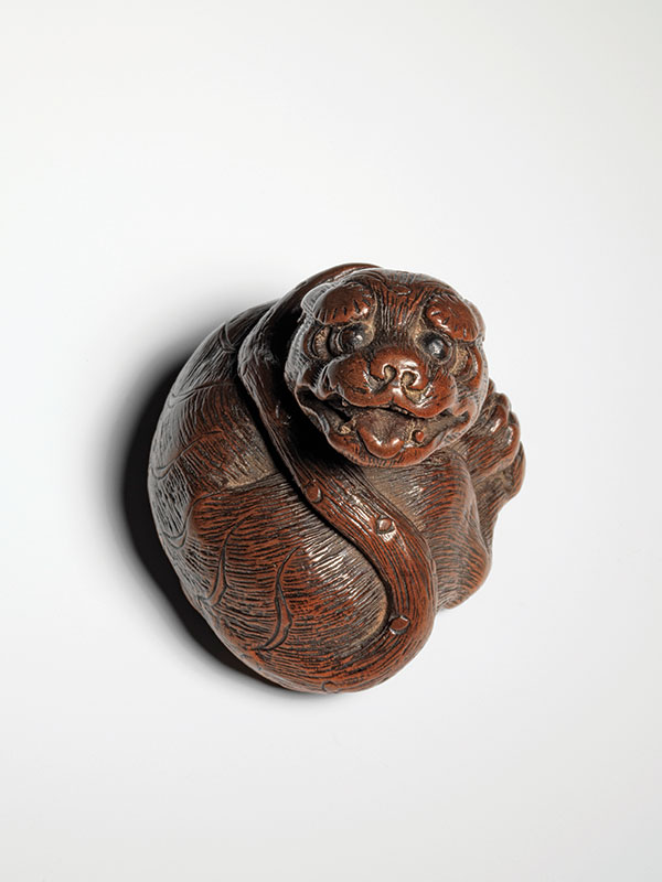 A powerful netsuke of a reclining tiger