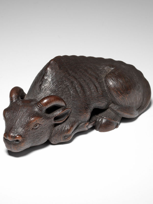 A dark stained wood reclining ox