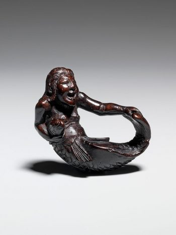 A ningyo (mermaid) grips her tail in one hand
