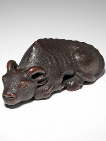 A dark-stained wood reclining ox