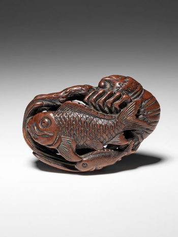 A boldly carved model of a group of fish encircled by a crayfish